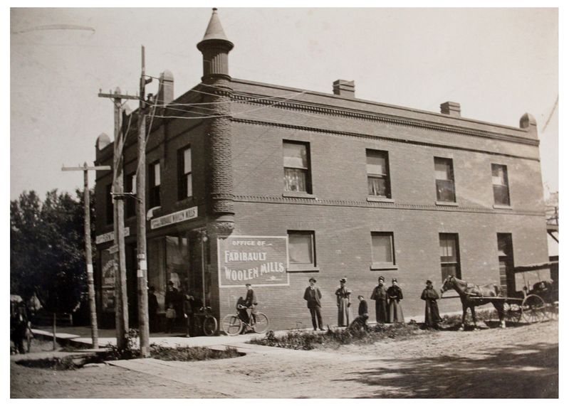 Faribault's founder, Carl H. Klemer (center of the image, under the window), in front of the old mill.
