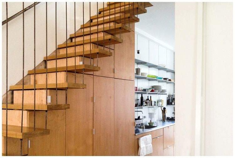 Space under the stairwell doubles as seamless custom cabinetry for kitchen storage