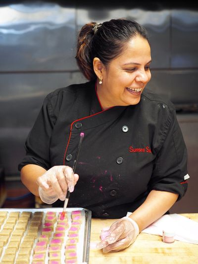 Chef Sahni brushes shimmer dust on a tray of kaju katli.