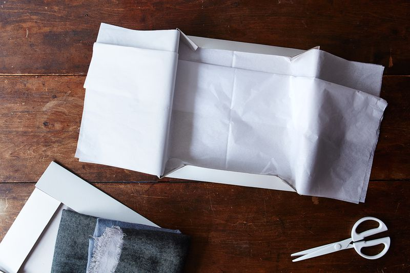 Tissue paper, doubled over at its middle, to wrap up the gift inside the box.
