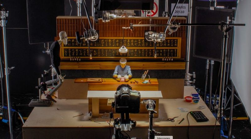 "The making of the sushi scene: Cameras capture a tiny sushi chef figurine hard at ""work""."