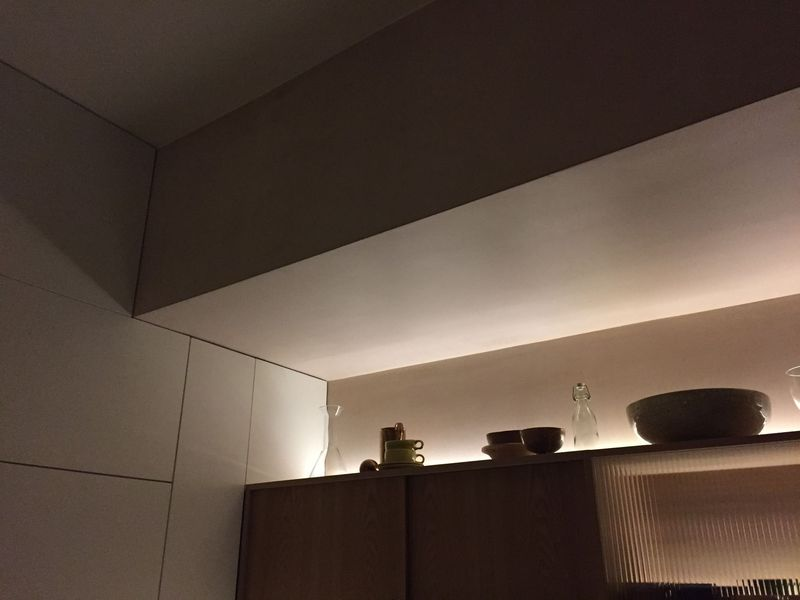 The lighting above and within the cabinets, at night.