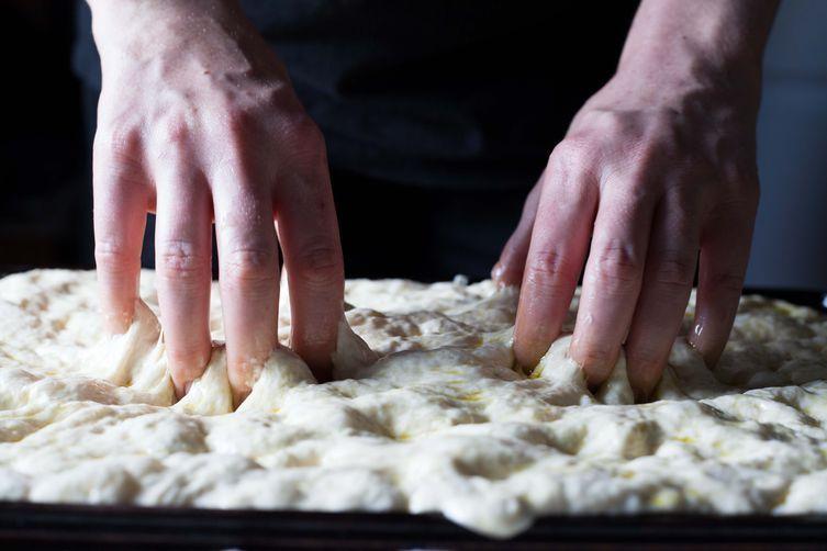 Patting focaccia dough