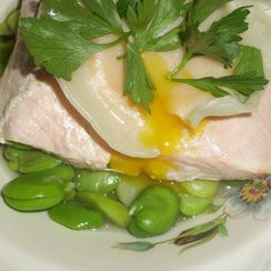 Poached salmon and fava beans in the broth with egg yolk ravioli