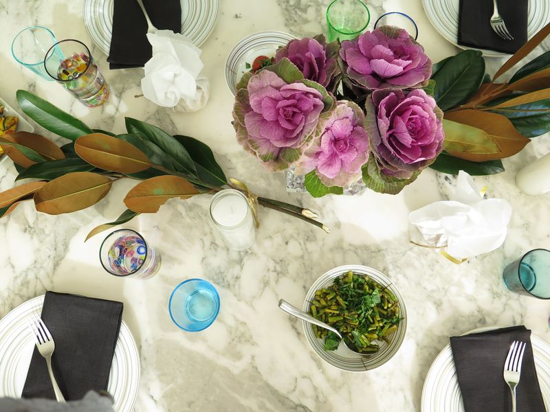 Neutral dishware, bright flowers, parchment-wrapped walnuts, and tall white candles make a festive table.