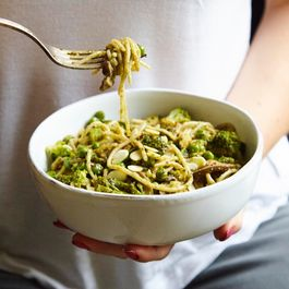 Brown rice pasta with broccoli, pesto, toasted almonds and peas