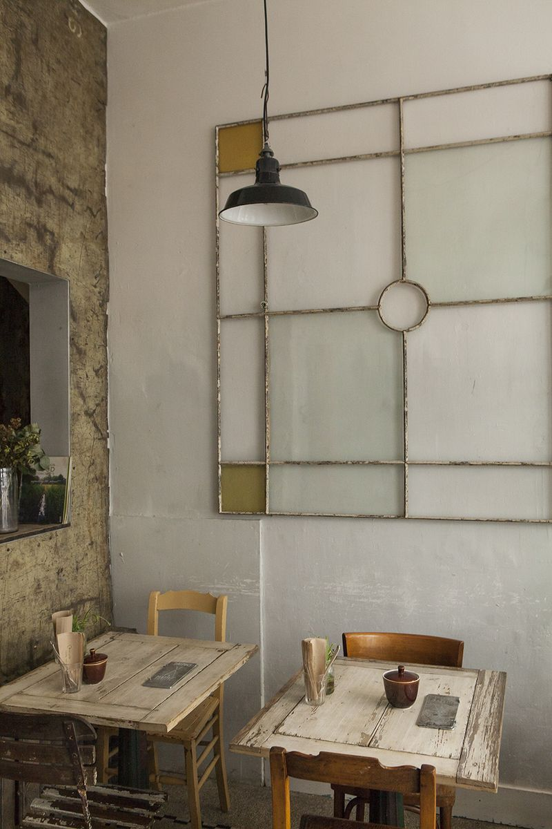 Pale stained glass against a white wall in Antwerp's Native Bistro, where waste-free extends from the menu to the design.