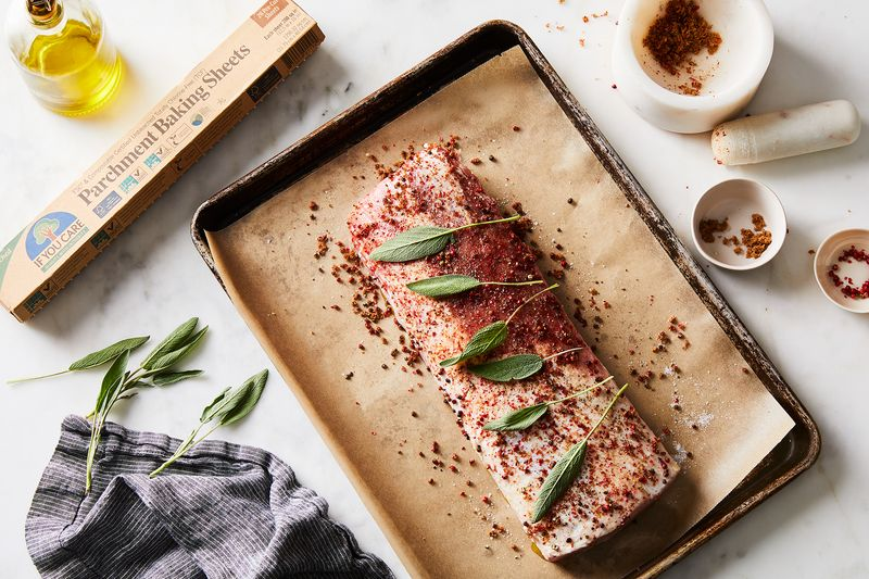 Wrap the pork loin in parchment paper to retain moisture and flavor while it roasts—and rests!