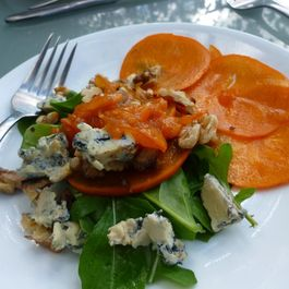An autumn salad of toasted walnuts over persimmon and salad greens