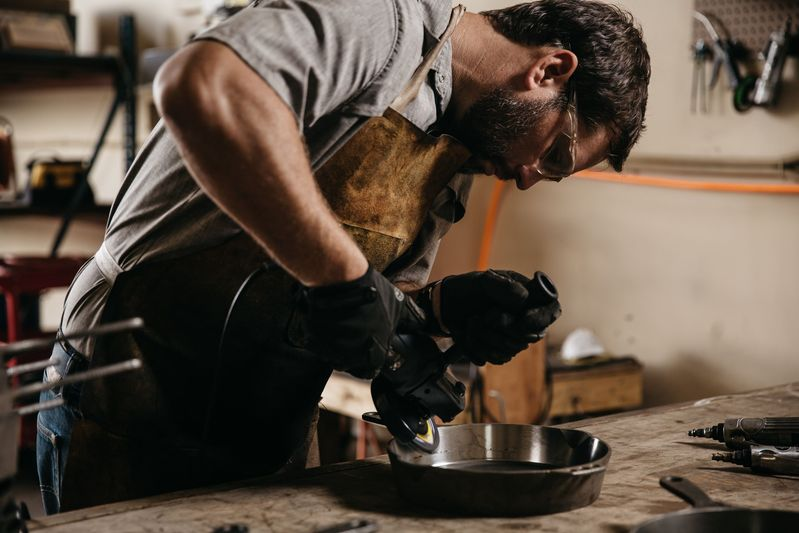 Isaac in his Charleston, South Carolina workshop, polishing a skillet to a gleaming shine.