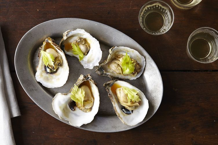 Oysters with Caramelized Honey, Tomato Broth, Celery Leaves, and Chili