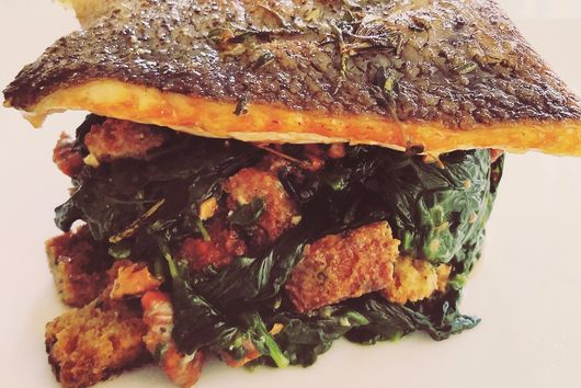 Crispy Salmon on a bed of Sautéed Spinach with croutons and walnuts