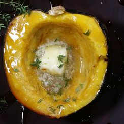 Baked acorn squash with butter, maple syrup and thyme