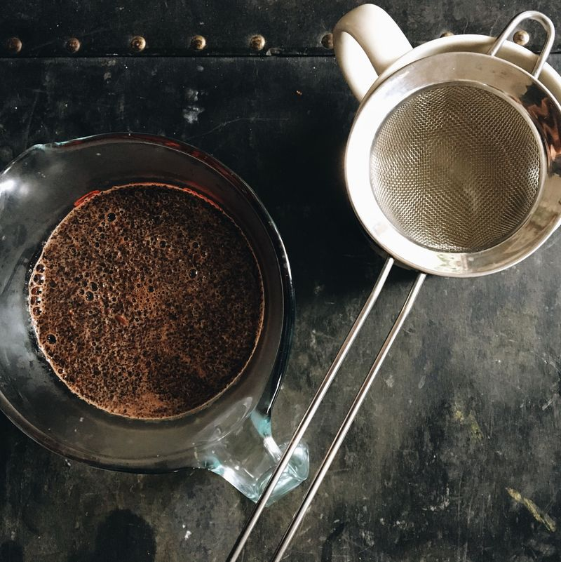 Coffee grounds a-steeping, sieve at the ready.