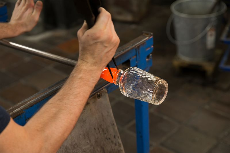 A glass maker creating a stem (and quickly, every second counts!).
