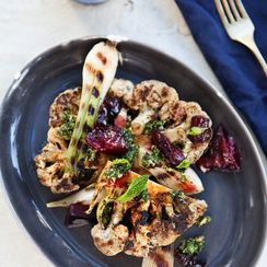 Togarashi grilled cauliflower with grilled spring onions and plums.