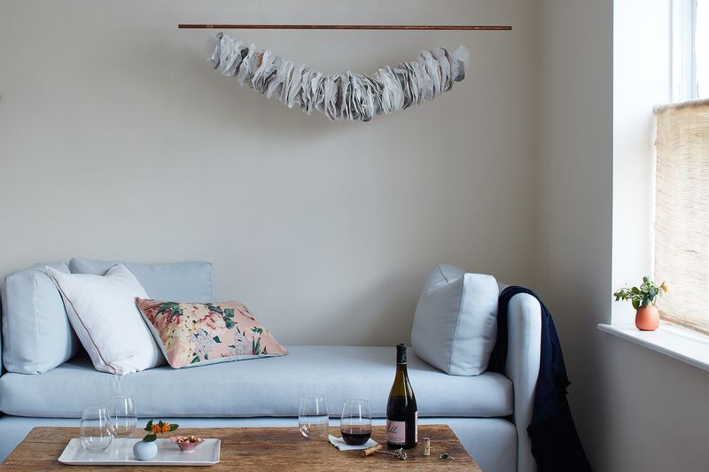 A hanging copper pipe with a party garland affixed to it.