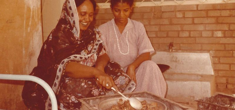 Eltigani's late grandmother cooking with a family member.