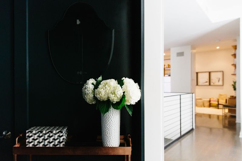 Dark paint gives the entryway a dramatic flair.