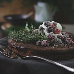 Chocolate rosemary Christmas cake decorated with cranberry fizzy balls