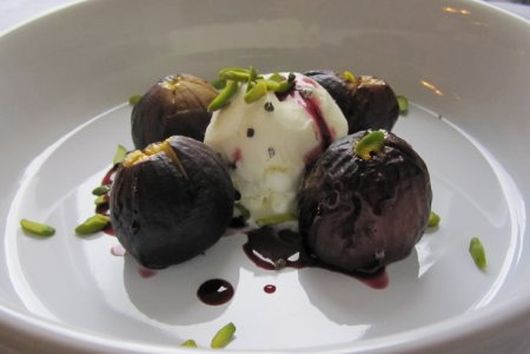 Roasted figs in a red wine cardamom-infused reduction with vanilla ice cream