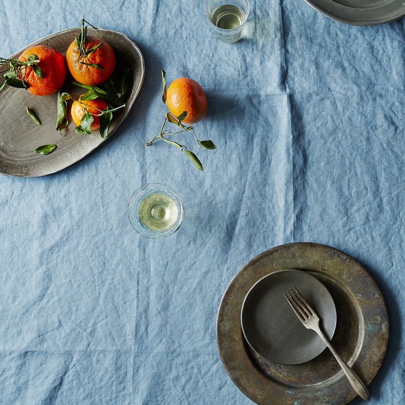 Celina Mancurti's blue linen tablecloth comes folded and tied with a woven tan ribbon.