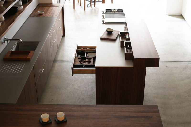 "The protruding part of the counter, called a ""Bar Block,"" houses storage but also serves as counter space."