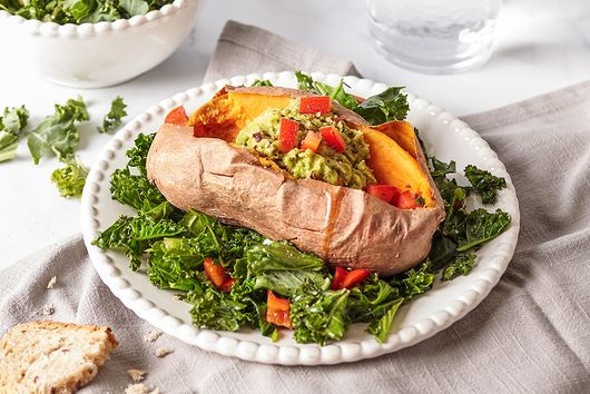 Stuffed sweet potatoes with avocado and kale salad