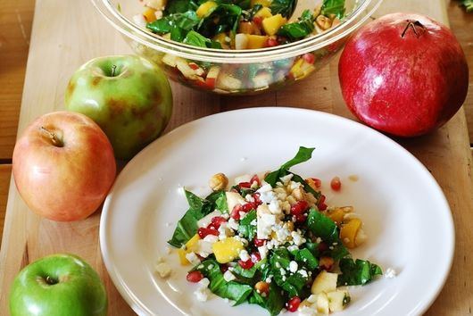 Chopped salad with apples, pears, mango, spinach, hazelnuts, and pomegranates