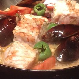 Sturgeon bathed in anchovy tomato sauce with Mediterranean friends
