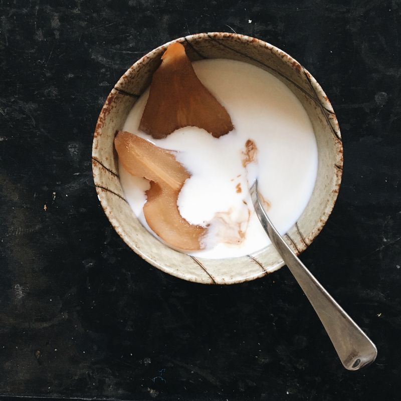 Poached pears take a dip in a bowl of yogurt.