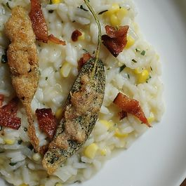 Corn Risotto Garnished with Bacon & Anchovy Sage Leaf Bite