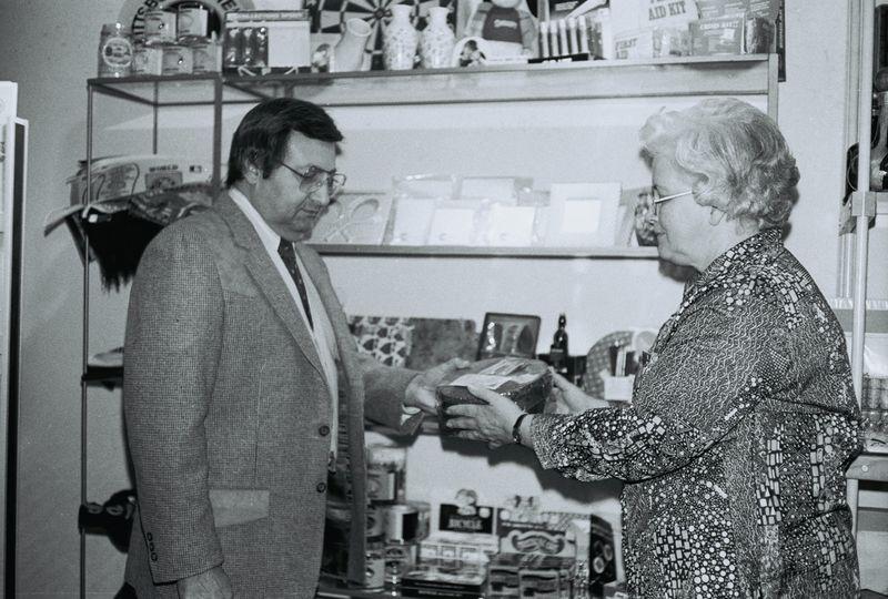 A woman who runs a gift store in Pennsylvania presents a fruitcake to mall executive.